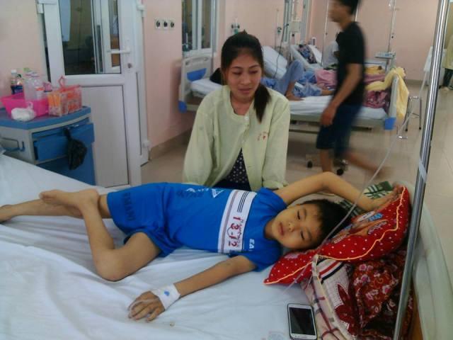 Chị Đỗ Thị Quế đang chăm sóc con trai mắc bệnh U đầu tụy tại bệnh viện K (Tân Triều - Hà Nội). Ảnh C.T