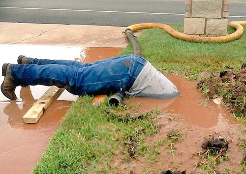 Jimmie Cox chúi đầu xuống vũng nước bùn cao đến thắt lưng để sửa đường ống nước. Ảnh: Twitter