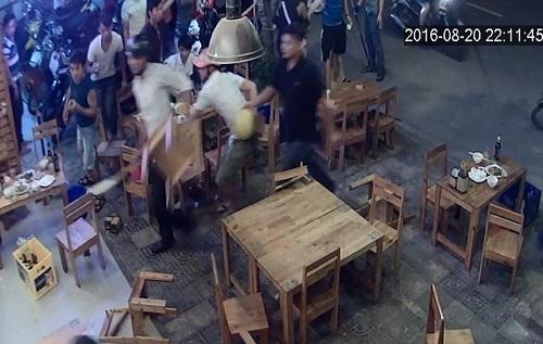 Nhóm thanh niên manh động cầm mã tấu xông vào quán đập phá, đuổi đánh người. Ảnh cắt từ camera.