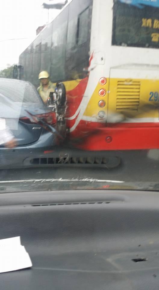 Xe máy của người phụ nữ mắc kẹt khi cố len qua 2 xe ô tô.