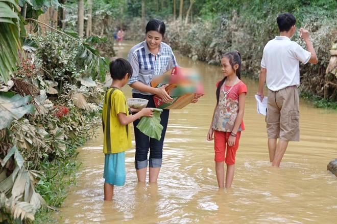 Ngọc Hân lội nước đến trao quà cho người dân. Ảnh: FBNV.