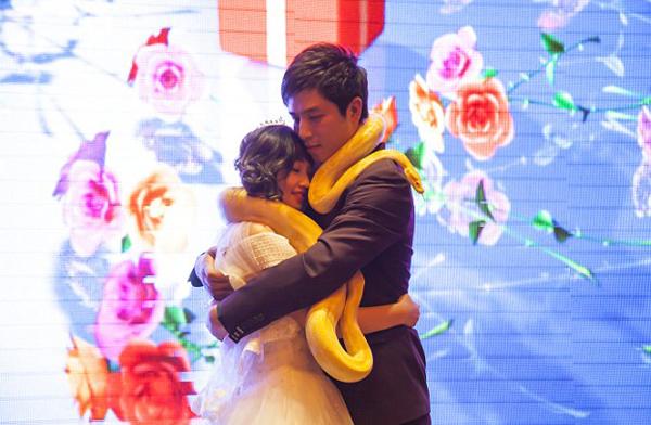 Cả hai ôm nhau hạnh phúc, trên cổ quàng hai con trăn. Ảnh: Rex