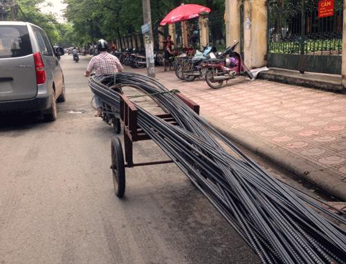 Chiếc xe máy thô sơ kéo theo phía sau là những thanh sắt dài cả gần chục mét.