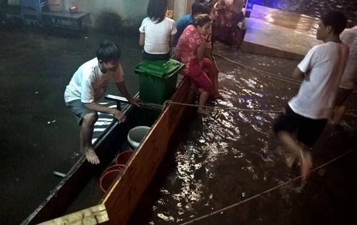 Một gia đình dùng ván cắn trước cửa để ngăn dòng nước ập vào nhà. Ảnh: Duy Trần