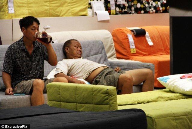 Một người đàn ông thì uống nước, người kia thì ngủ phơi cả bụng ngay trên những sofa của siêu thị.