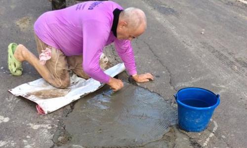 Ông Peter Goman vá lại ổ gà trên con đường gần nhà ở tỉnh Buriam, Thái Lan. Ảnh: BBC
