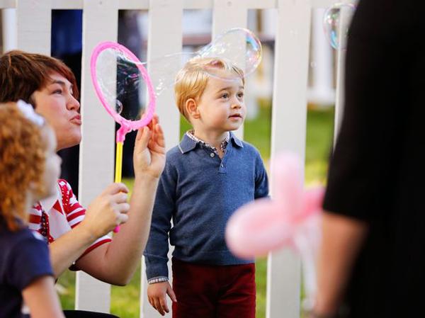 Hoàng tử nhí thích thú với trò thổi bóng bay.