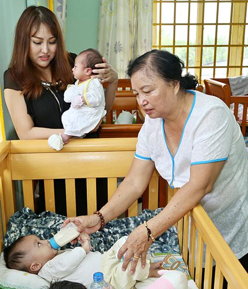 Mẹ ruột của nữ diễn viên cũng tham gia chuyến đi. Bà ân cần chăm sóc, cho một bé còn nằm nôi bú sữa bình.