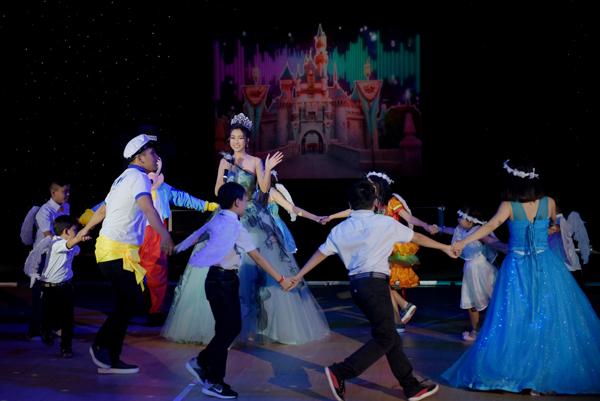Hoa hậu vào vai Cinderella, cùng hát và trình diễn tiết mục mở màn với các bé thiếu nhi Việt Nam.