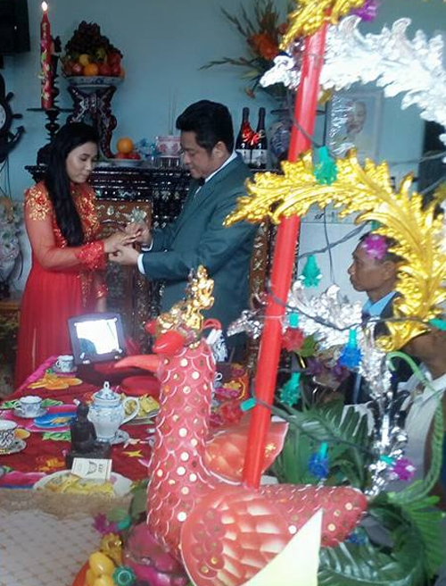 Chú rể và cô dâu trao nhẫn cưới cho nhau khi thực hiện nghi lễ gia tiên ở nhà gái.