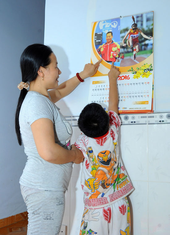 Chị Tám và hai con tự hào về những hình ảnh của bố trên tờ lịch treo trong nhà.