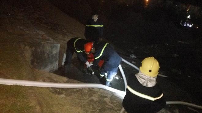 Cảnh sát bơm nước từ sông Tô Lịch lên chữa cháy.