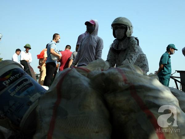 2 người phụ nữ bịt kín khẩu trang, áo chống nắng này đòi mang những bao tải cá chết đi để bón cây, cho lợn ăn nhưng bị lực lượng chức năng ngăn cản và yêu cầu không ai được mang bất cứ con cá nào đi bởi lo ngại dịch bệnh lây lan. Ảnh chụp sáng 3/10.