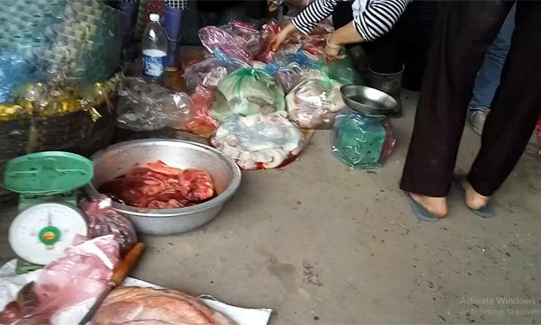 Thịt lợn, lòng, mỡ bẩn vứt chỏng chơ dưới đất trong chợ.