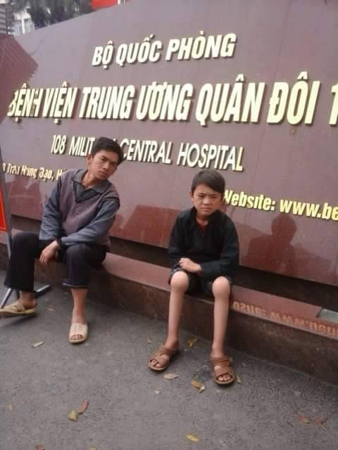 Bé Vừ Mí Pó mệt mỏi, đau đớn vì bệnh trọng cùng bố ở cổng Bệnh viện TƯQĐ 108. Ảnh: Mít Giàng