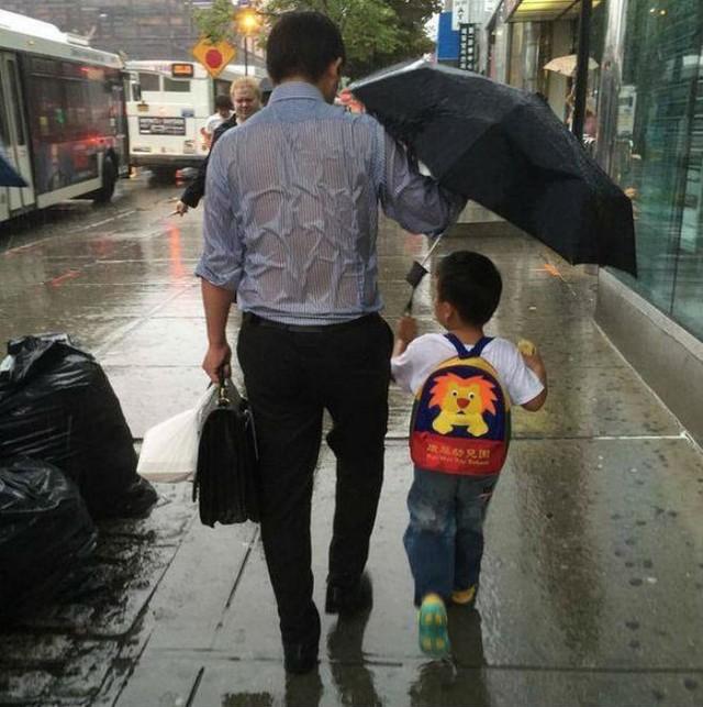 Bức ảnh ông bố toàn thân ướt sũng, che ô cho con trai gây xúc động trong cộng đồng mạng thế giới. Ảnh: CCTV News.