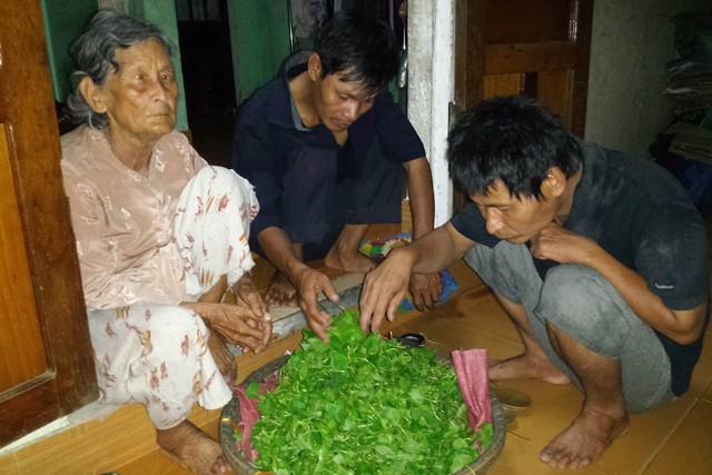Cụ Nguyễn Thị Tồn cùng các con Phạm Thiện (ở giữa) và Phạm Cu nhặt rau để chuẩn bị hàng cho ngày mai. Ảnh: Đ.H
