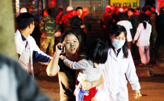 Những đứa trẻ được lực lượng PCCC đưa xuống đất an toàn trong vòng tay người thân.