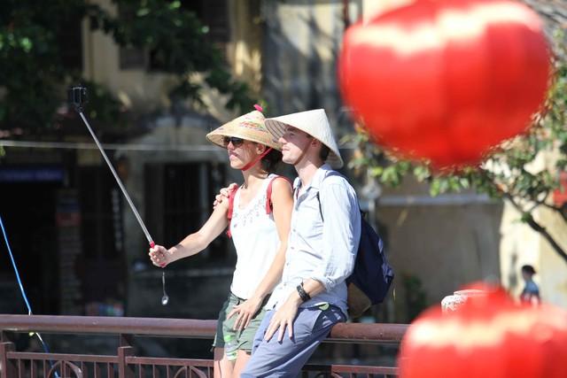 Hai du khách nước ngoài đang chụp ảnh selfie bên những chiếc đèn lồng thơ mộng...