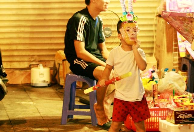 Sẽ rất nguy hiểm khi trẻ đeo những loại mặt nạ nhiều màu sắc, vì khi đó bé dễ hít phải những hạt bụi màu li ti bay ra trong quá trình vui chơi.  Ảnh: Chí Cường