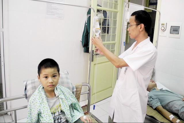 BS Hà Huy Tình kiểm tra truyền dịch cho bệnh nhi điều trị nội trú tại Khoa Truyền nhiễm, Bệnh viện Đa khoa Đống Đa. Ảnh: T.Nguyên