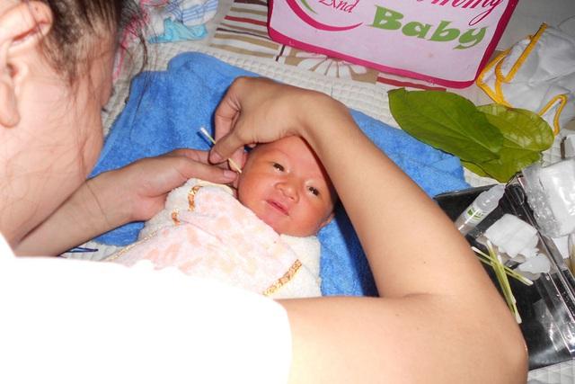 Với trẻ nhỏ hàng ngày sau khi tắm, bạn chỉ cần dùng khăn hoặc lấy tăm bông lau nhẹ vùng tai ngoài là đủ. Ảnh minh họa