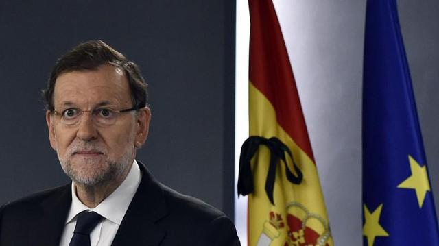 Thủ tướng Tây Ban Nha, Miano Rajoy, tổ chức buổi họp báo sáng nay (14/11). Đằng sau ông, lá quốc kỳ Tây Ban Nha và cờ Liên minh châu Âu đều được treo rủ, kèm theo ruy băng đen.