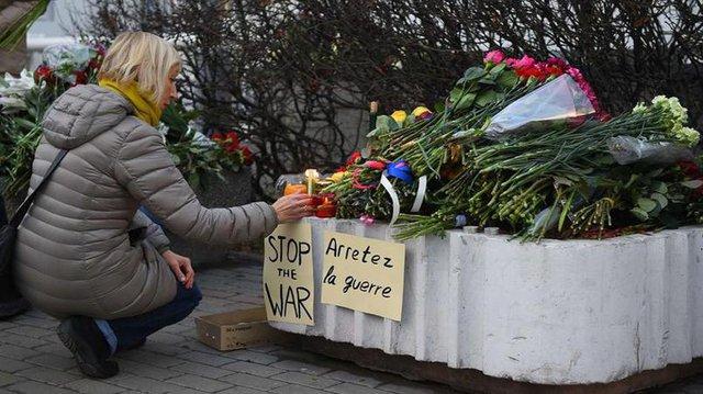 Một người phụ nữ thắp nến trước cửa Đại sứ quán Pháp tại Moscow (Nga).