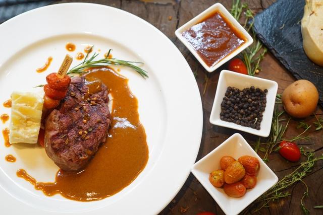 Bò Mỹ nướng thảo mộc ăn kèm với khoai tây cắt lát và sốt gan ngỗng của Moo Beef Steak từng chinh phục nhiều thực khách sành ăn.