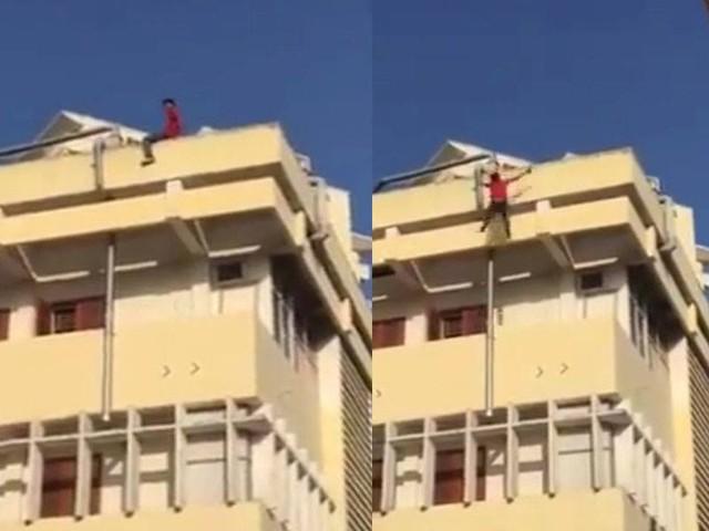Hình ảnh nam sinh trên nóc nhà 4 tầng (ảnh cắt từ clip).