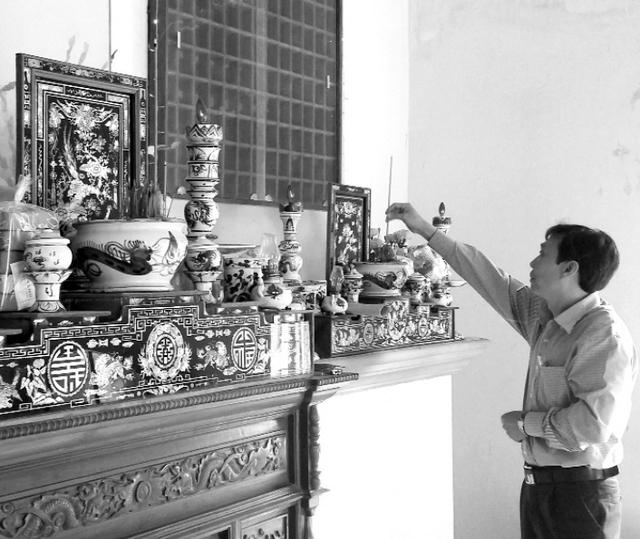 Ông Tuấn thắp nén hương lên bàn thờ trong nhà tang lễ của Trung tâm Nuôi dưỡng người tâm thần Hoài Nhơn.