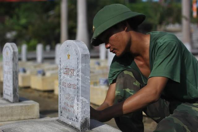 Chiến sĩ Trung đoàn 335, Sư đoàn 324 lau chùi mộ đồng đội chưa biết tên tại nghĩa trang Việt - Lào. Ảnh: Nguyễn Hồng Quân