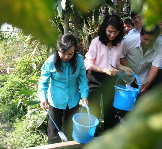 Bộ trưởng Y tế cùng Phó Chủ tịch TP.HCM giúp thả cá diệt loăng quăng tại một hộ gia đình.