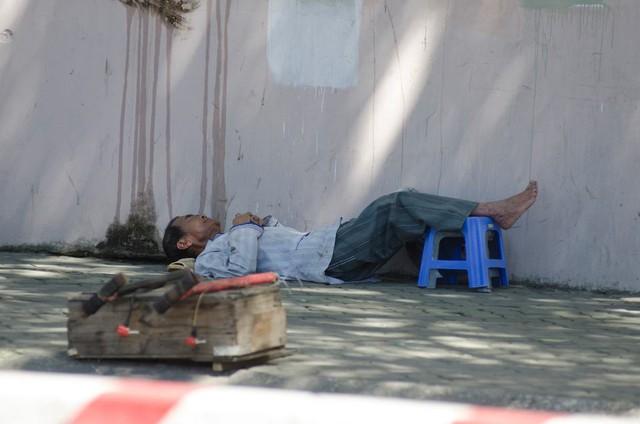Một người thợ sửa xe tranh thủ nằm nghỉ ngơi lúc vắng khách.