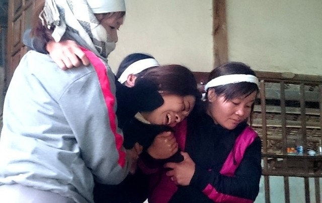 Chị Túc - vợ anh Trương Văn Danh khóc ngất trước sự ra đi đột ngột của chồng. Ảnh: Nguyễn Dương.