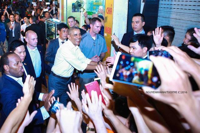 Sau khi dùng bữa tối dân dã tại cửa hàng bún chả, ông bước ra và mỉm cười, bắt tay thân thiện với những người dân Hà Nội. Nguồn: Nguyễn Khánh/Tuổi Trẻ.