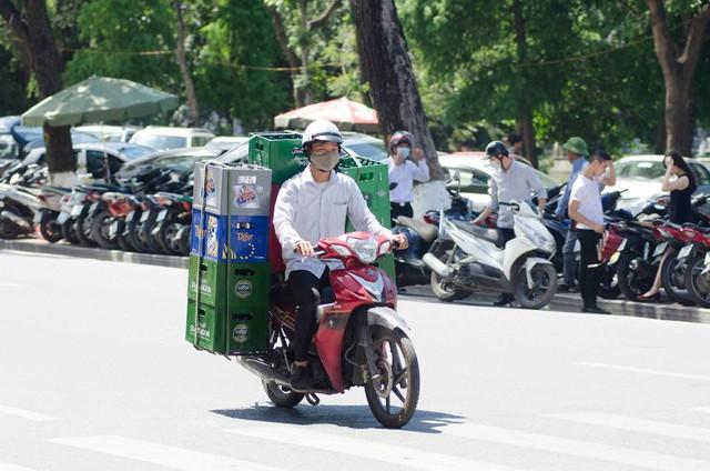 Một người đàn ông chở bia vẫn miệt mài với công việc dưới cái nóng bỏng lưng.