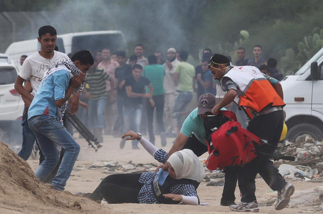 Nữ nhà báo ngã xuống đất sau khi hít phải khí hơi cay do lính Israel phun ra trong cuộc đụng độ với người biểu tình gần biên giới giữa Israel và dải Gaza ngày 23/10/2015.