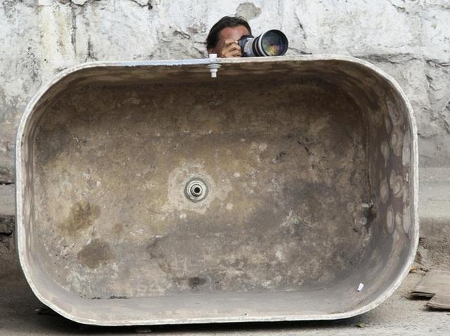 Một phóng viên ẩn náu phía sau thùng đựng nước trống để ghi lại những khoảnh khắc chân thực trong cuộc truy quét tội phạm ở khu ổ chuột Alemao, Rio de Janeiro vào ngày 27/11/2010.