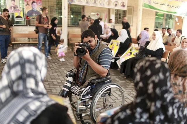 Phóng viên tự do Moamen Oreiqea chụp ảnh những người tham gia biểu tình kêu gọi phía Israel thả các tù nhân Palestine. Oreiqea (25 tuổi) đã buộc phải cắt bỏ hai chân sau khi bị thương trong một cuộc không kích hồi năm 2008 trong lúc đi chụp ảnh ở phía đông Gaza. Người cha của 2 đứa con này cho biết dù tàn tật, anh vẫn quyết tâm theo đuổi ước mơ chụp ảnh của mình.