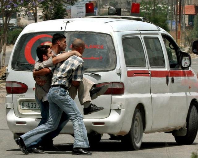 Những người dân Palestine đang bế một phóng viên quay phim bị thương trong lúc anh tác nghiệp ở thị trấn Jenin ngày 24/5/2005.
