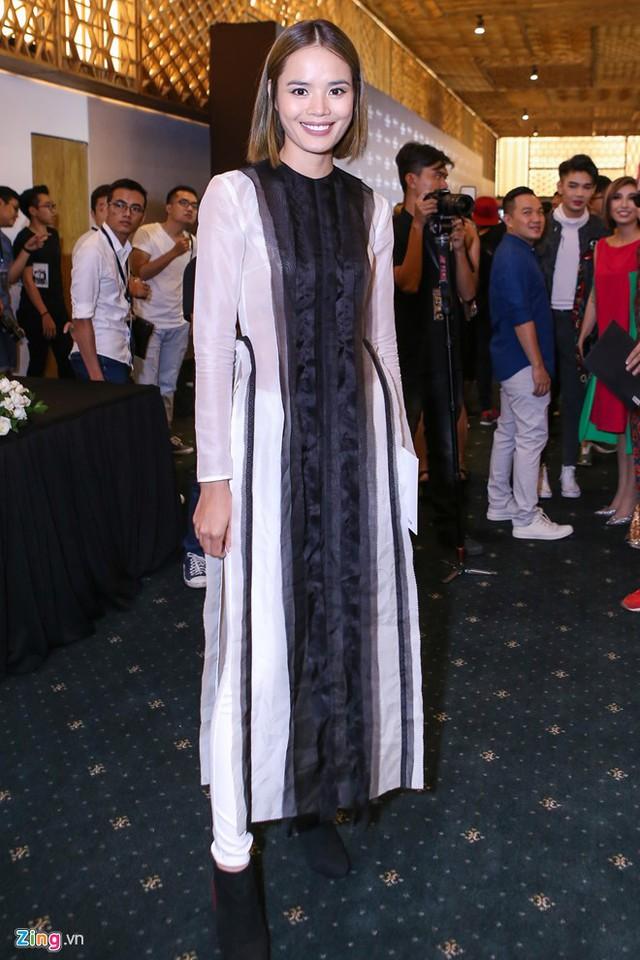 Thu Hiền chọn áo dài của NTK Nguyễn Hoàng Tú, phối kèm quần jeans trắng, boots cổ ngắn.