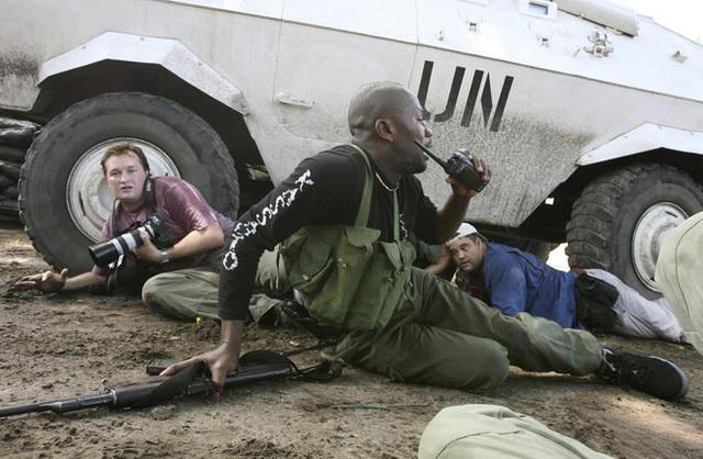 Phóng viên người Congo của hãng Reuters David Lewis (trái) đang ẩn náu sau chiếc ô tô của Liên Hợp Quốc trong cuộc đấu súng ở Kinshasa ngày 11/11/2006.
