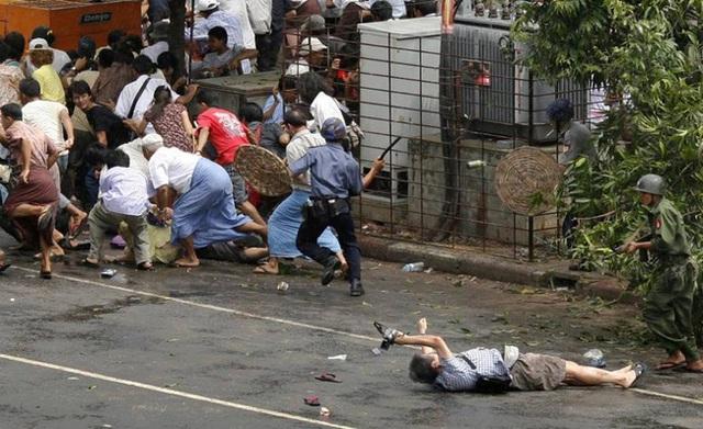 Phóng viên người Nhật Kenji Nagai của hãng AFP đang cố gắng ghi lại những khoảnh khắc đắt giá dù đã bị thương và nằm soài trên nền đất. Trong ảnh: Lực lượng cảnh sát nổ súng để giải tán nhóm người biểu tình ở trung tâm thành phố Yangon, Myanmar vào ngày 27/9/2007.