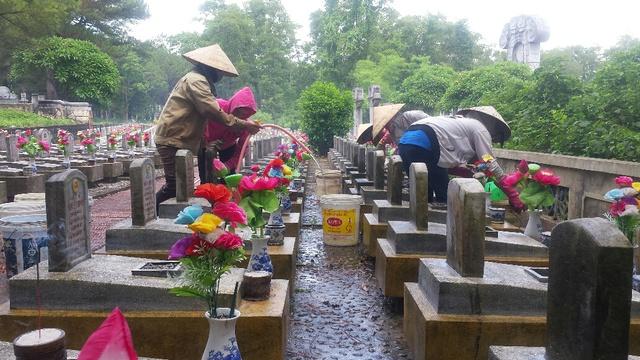 Giữa dòng người thăm viếng, ở một góc nghĩa trang những người quản trang vẫn tất bật với công việc làm sạch đẹp nơi yên nghỉ của các anh hùng liệt sĩ. Ảnh: Lê Chung