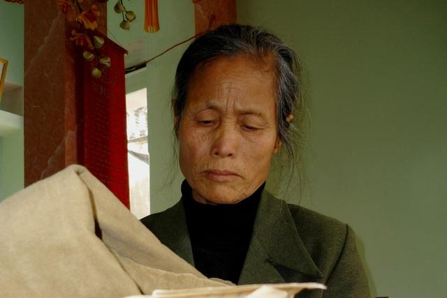 Bà Lê Thị Chạy – vợ liệt sĩ Đoàn Anh Thông bên những lá thư của chồng. Ảnh: Lữ Mai