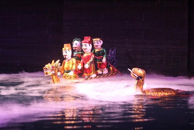 Truyền thuyết Hồ Gươm được tái hiện trên sân khấu múa rối nước. Đằng sau tấm mành tre là các nghệ sĩ đang ngâm mình dưới bể nước để điều khiển các con rối.