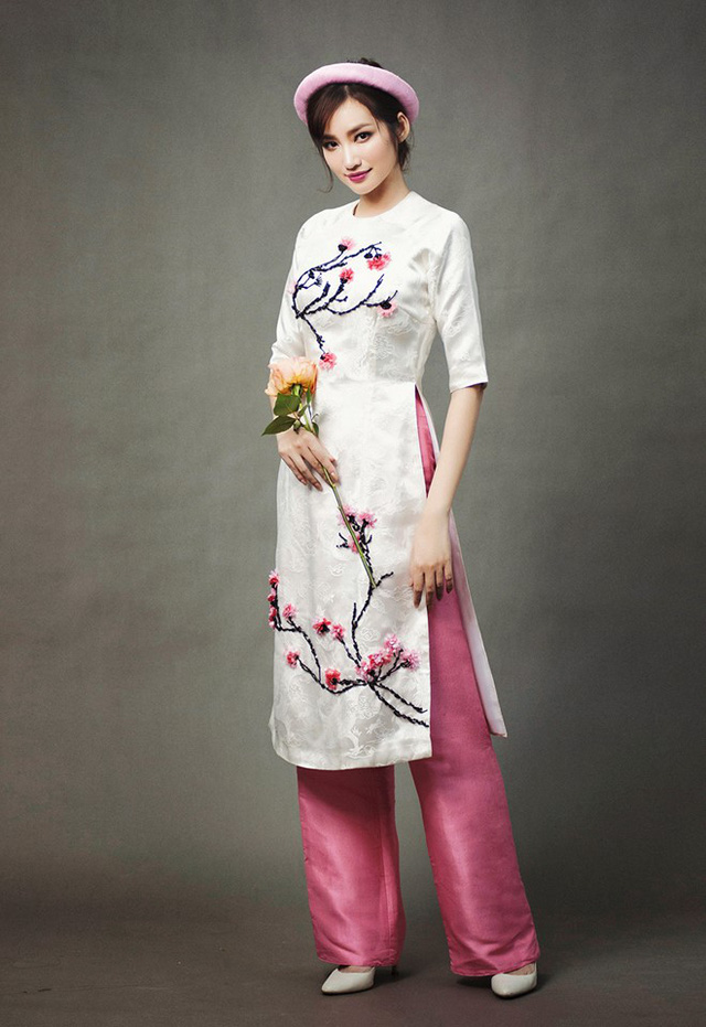 Một trong những bộ cánh mùa xuân nên mặc trong dịp Tết Nguyên đán mà người đẹp sinh năm 1987 muốn giới thiệu đến công chúng. Áo dài gấm trắng phối quần lụa tafta hồng cánh sen tinh tế.