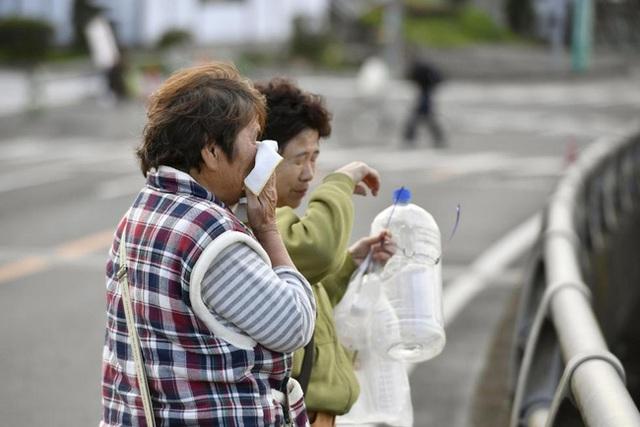 Một người phụ mữ đau đớn nhìn về căn nhà bị đổ sập của mình.