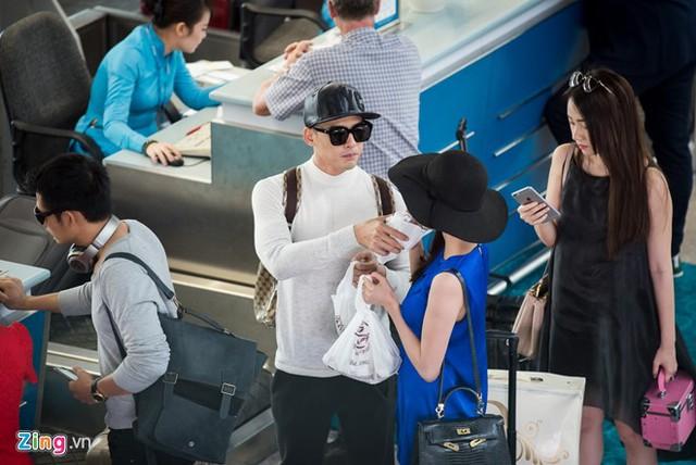 Anh còn đưa ly nước cho vợ uống trong khi cô lỉnh kỉnh với túi đồ trên tay.